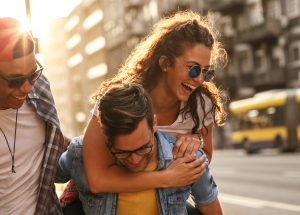 Group of friends hangout at the city street.They embrace each other and laughing.One man carrying female friend on his back. - AdobeStock 293825517 e1576086652837 300x215